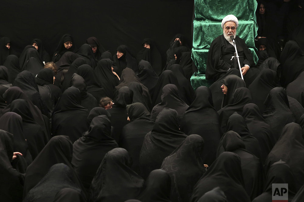 An Iranian Shiite cleric speaks to women mourners during a ceremony at Sadat Akhavi Mosque in Tehran, Iran, Sunday, Oct. 9, 2016, three days prior to the death anniversary of 7th century Shiite Imam Hussein, the grandson of Prophet Muhammad, who was killed in a battle in Karbala in present-day Iraq. (AP Photo/Ebrahim Noroozi)