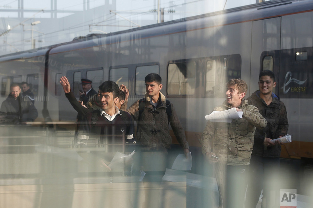 A Syrian and five Afghan boys wave on the platform of the Calais train station, northern France, as they leave for Britain, Thursday, Oct. 13, 2016. A group of young migrants is leaving the French city for Britain, as both governments seek solutions for hundreds of unaccompanied children in Calais' migrant camp before it is shut down in the coming weeks. (AP Photo/Thibault Camus)