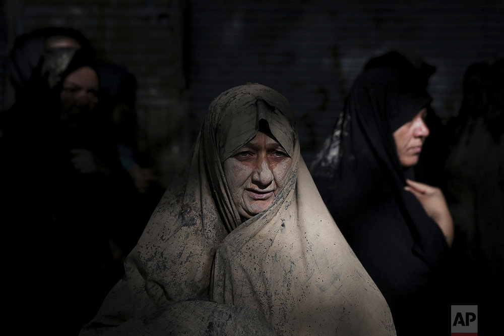 An Iranian Shiite Muslims mourns after covering herself with mud during Ashoura rituals at the city of Khorramabad, Iran, Wednesday, Oct. 12, 2016. Shiites mark Ashoura, the tenth day of the Muslim month of Muharram, to commemorate the martyrdom of Imam Hussein, a grandson of Prophet Muhammad and one of Shiite Islam's most beloved saints, during the 7th century Battle of Karbala in present-day Iraq. (AP Photo/Ebrahim Noroozi)