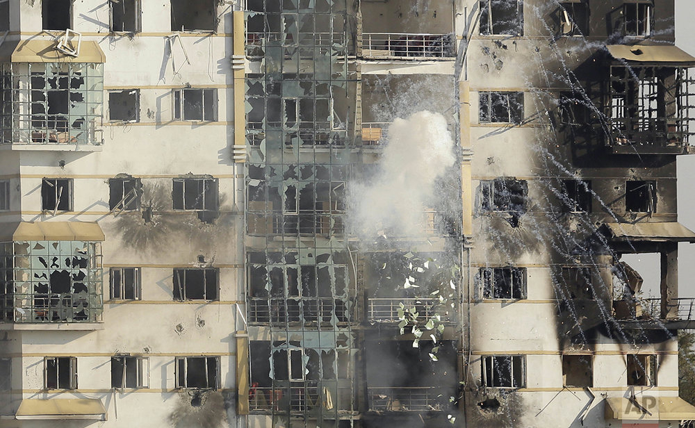 An explosive hits a building where suspected militants have taken refuge during a gun battle in Pampore, on the outskirts of Srinagar, Indian controlled Kashmir, Tuesday, Oct. 11, 2016. A handful of rebels holed up in the building in the Indian portion of Kashmir exchanged fire with government forces for the second straight day on Tuesday. (AP Photo/Mukhtar Khan)