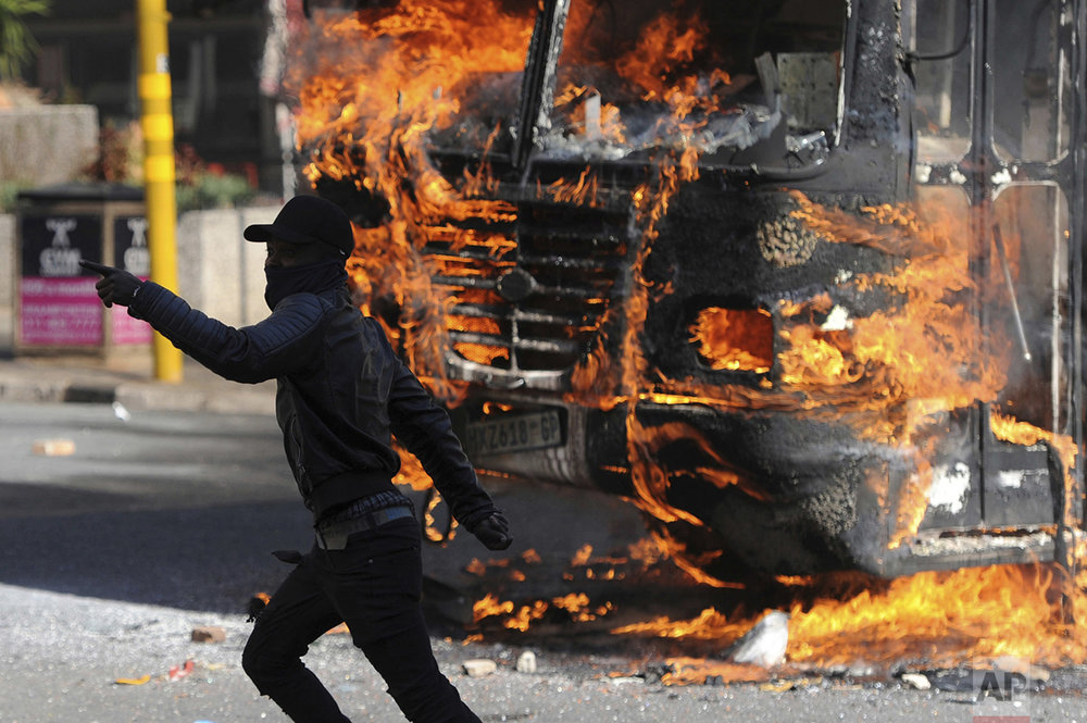 A protesting student runs past a burning bus near the University of the Witwatersrand in Johannesburg, South Africa on Monday, Oct. 10, 2016. Tear gas and water cannons were fired as hundreds of students protested at the school amid a bitter national dispute with university managers and the government over demonstrators' demands for free education, forcing students into the neighboring city streets. (AP Photo)