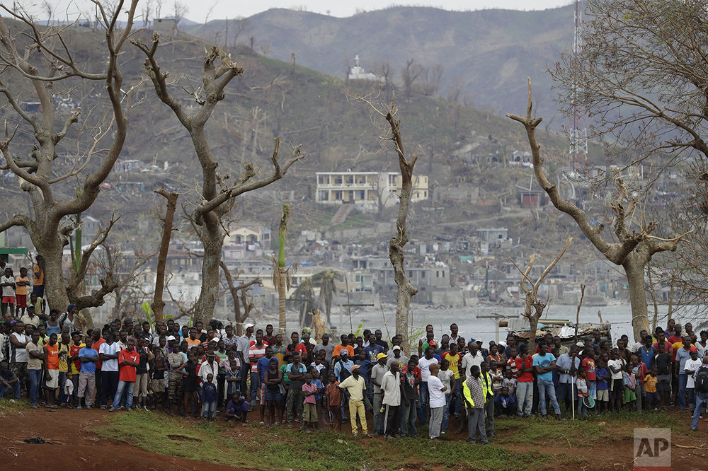 Town residents gather to watch as U.S. military personnel unload USAID relief supplies from a helicopter in Anse d'Hainault, southwestern Haiti, Friday, Oct. 14, 2016. Two U.S. military helicopters touched down briefly on Friday morning to deliver drinking water and saline to the remote town, which has seen a spike in cholera cases after suffering severe damage from Hurricane Matthew. (AP Photo/Rebecca Blackwell)