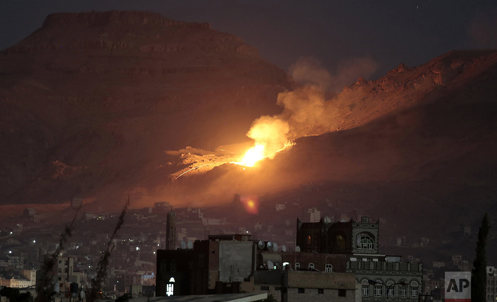Fire and smoke rise after a Saudi-led airstrike hit a site believed to be one of the largest weapons depots on the outskirts of Yemen's capital, Sanaa, Friday, Oct. 14, 2016. Yemen, on the southern edge of the Arabian Peninsula, has been in the midst of a civil war since September 2014 when Shiite rebels, known as Houthis, swept into the capital and overthrew the country's internationally recognized government. (AP Photo/Hani Mohammed)
