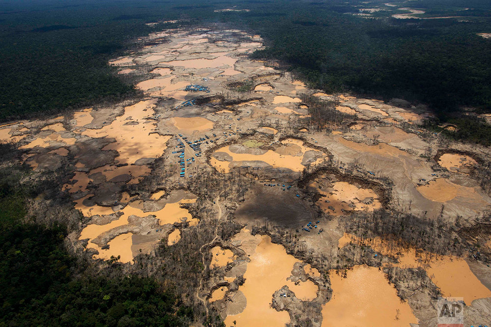 This Nov. 11, 2014 photo shows a deforested area dotted with blue tarps, marking the area where miners reside, and craters filled with water, caused by illegal gold mining activities, in La Pampa, in Peru's Madre de Dios region. Peru's government declared an emergency across a broad jungle region because of mercury contamination, much of it caused by wildcat gold mining.  (AP Photo/Rodrigo Abd)