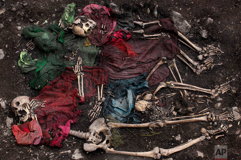 In this Nov. 13, 2013 photo, the scattered remains of five skeletons are unearthed during an exhumation of a mass grave in the district of Chungui, Peru. This isolated corner of Peru is witnessing the biggest exhumation to date of victims of the nation's 1980-2000 internal conflict, which claimed an estimated 70,000 lives. (AP Photo/Rodrigo Abd)