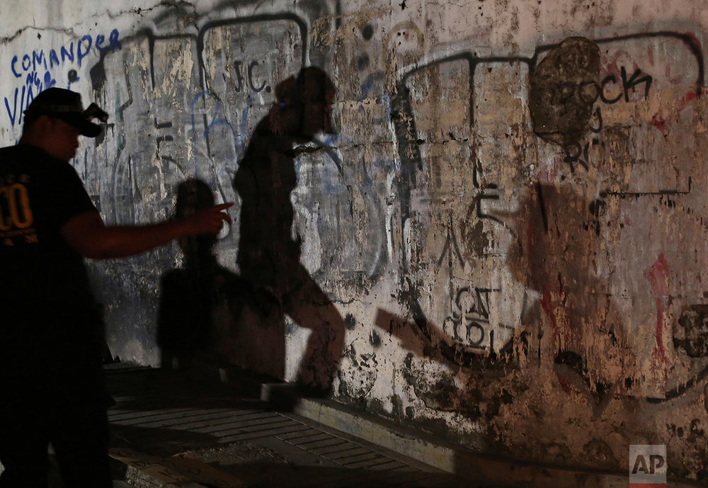 In this Sept. 21, 2016 photo, the shadows of police investigators are reflected on a wall as they check an unidentified body of an alleged drug lord after it was dumped along a dark alley in Manila, Philippines.  (AP Photo/Aaron Favila)