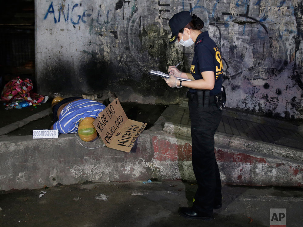 "In this Sept. 21, 2016 photo, a police investigator checks on the unidentified body of an alleged drug lord with his head, hands and feet wrapped in packaging tape and with a cardboard sign that reads ""Kage Lao, Drug Lord of Mindanao, You will be next!"" after it was dumped by unidentified men along a dark alley in Manila, Philippines. (AP Photo/Aaron Favila)"