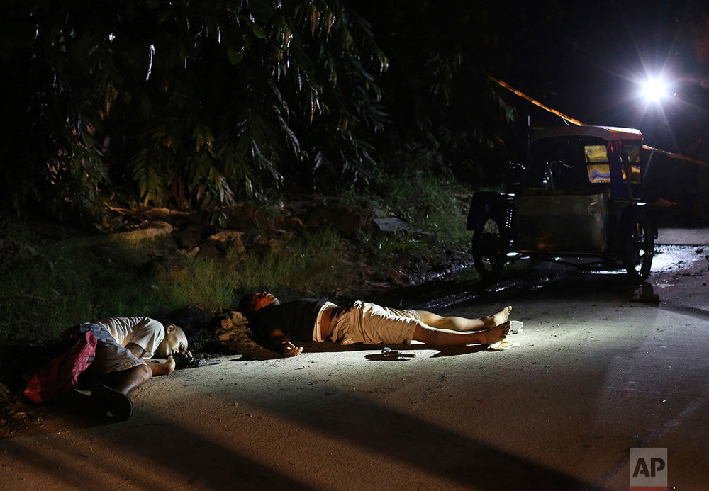 In this Sept. 6, 2016 photo, two unidentified drug suspects lie on the ground after being shot by police as they tried to evade a checkpoint in Quezon city, north of Manila, Philippines. (AP Photo/Aaron Favila)