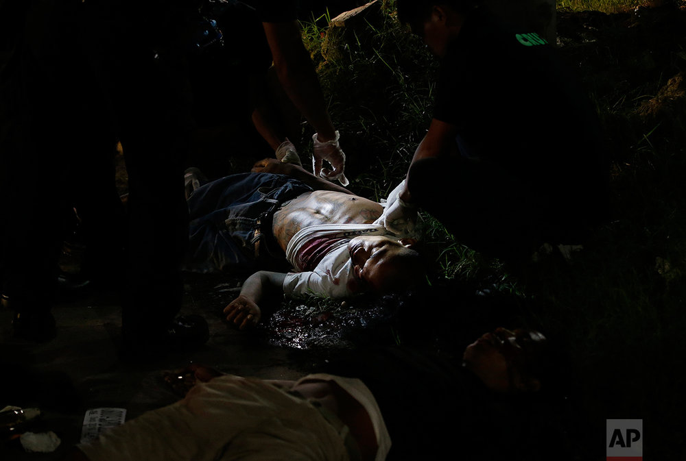 In this Sept. 6, 2016 photo, police inspect one of two unidentified drug suspects after being shot by police as they tried to evade a checkpoint in Quezon city, north of Manila, Philippines. (AP Photo/Aaron Favila)