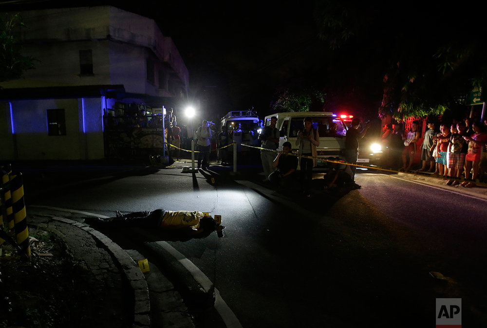 In this Sept. 5, 2016 photo, the body of alleged drug user Marcelo Salvador lies on the pavement after being shot by unidentified men in Las Pinas, south of Manila, Philippines. Drug dealers and drug addicts, were being shot by police or slain by unidentified gunmen in mysterious, gangland-style murders that were taking place at night. Salvador became a victim, the casualty of a vicious war on drugs that has claimed thousands of lives as part of a campaign by Philippine President Rodrigo Duterte. (AP Photo/Aaron Favila)