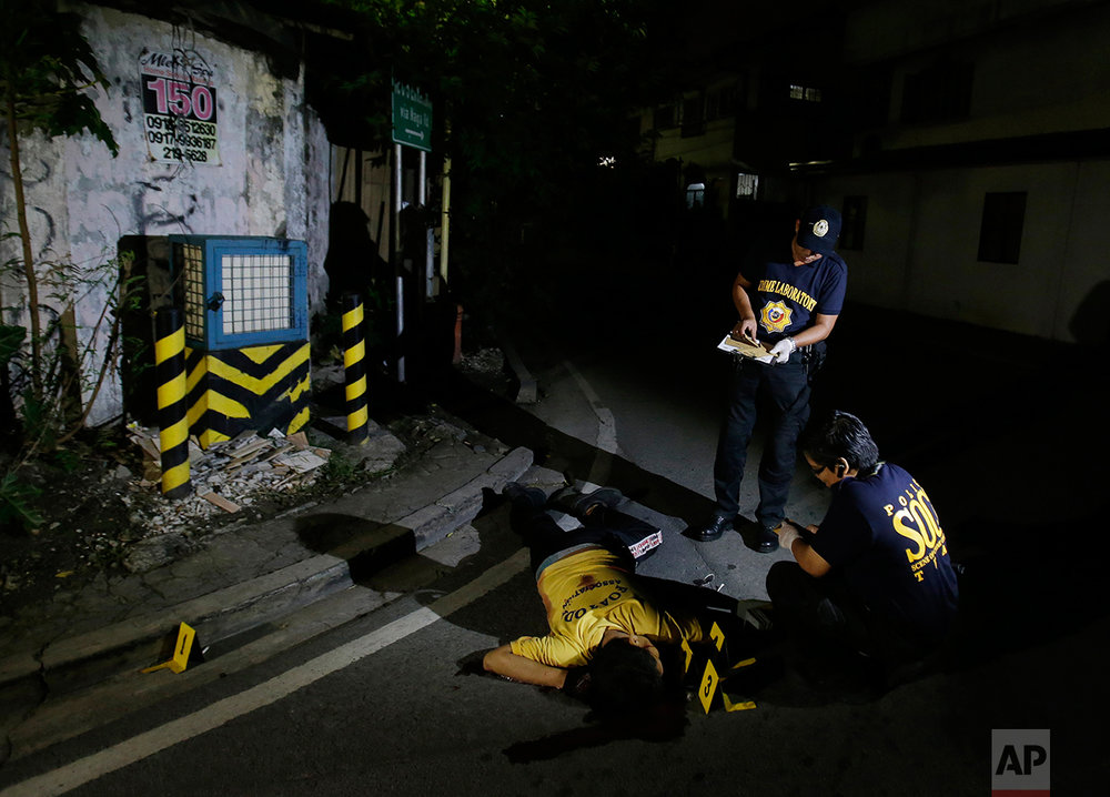 In this Sept. 5, 2016 photo, police investigators inspect the body of alleged drug user Marcelo Salvador after being shot by unidentified men in Las Pinas, south of Manila, Philippines. Drug dealers and drug addicts, were being shot by police or slain by unidentified gunmen in mysterious, gangland-style murders that were taking place at night. Salvador became a victim, the casualty of a vicious war on drugs that has claimed thousands of lives as part of a campaign by Philippine President Rodrigo Duterte. (AP Photo/Aaron Favila)