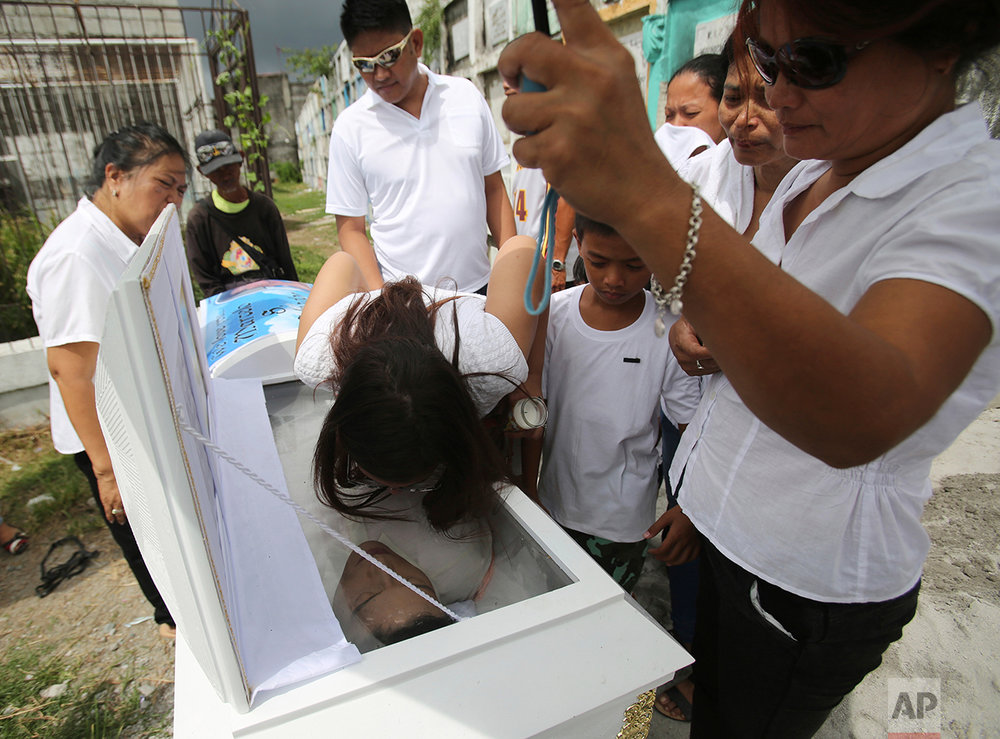 In this Sept. 14, 2016 photo, Ruzaina Romero, the sister of alleged drug user Marcelo Salvador kisses his coffin during funeral rites at the public cemetery in Las Pinas, south of Manila, Philippines. Drug dealers and drug addicts, were being shot by police or slain by unidentified gunmen in mysterious, gangland-style murders that were taking place at night. Salvador became a victim, the casualty of a vicious war on drugs that has claimed thousands of lives as part of a campaign by Philippine President Rodrigo Duterte. (AP Photo/Aaron Favila)