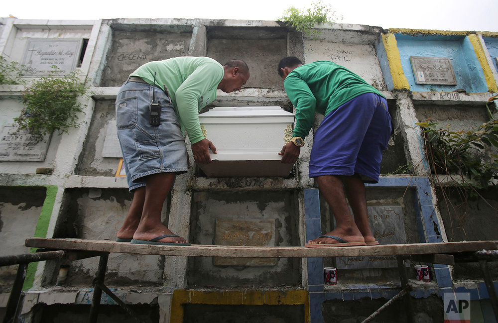 In this Sept. 14, 2016 photo, cemetery workers carry the coffin of alleged drug user Marcelo Salvador, Betchie during funeral rites in Las Pinas, south of Manila, Philippines. Drug dealers and drug addicts, were being shot by police or slain by unidentified gunmen in mysterious, gangland-style murders that were taking place at night. Salvador became a victim, the casualty of a vicious war on drugs that has claimed thousands of lives as part of a campaign by Philippine President Rodrigo Duterte. (AP Photo/Aaron Favila)