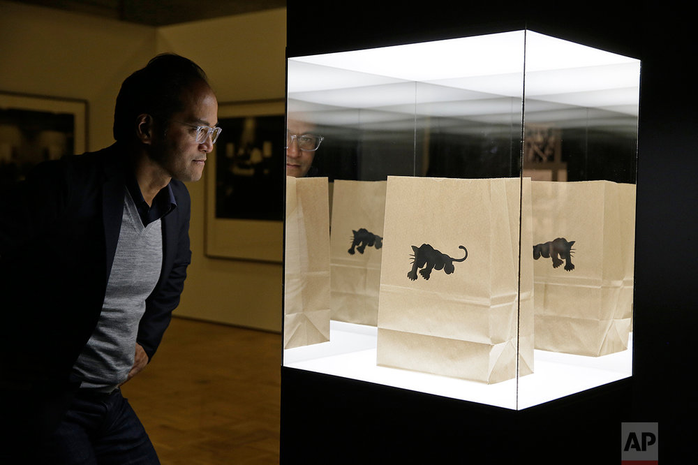 "In this photo taken Monday, Oct. 3, 2016, senior curator Rene de Guzman looks over a bag used by the Black Panther Party to give away food in the exhibition called ""All Power to the People: Black Panthers at 50"" at the Oakland Museum of California in Oakland, Calif. (AP Photo/Eric Risberg)"