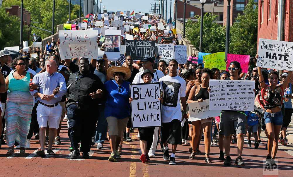 In this Sunday, July 10, 2016  photo, people march in a Black Lives Matter rally in Oklahoma City. (AP Photo/Sue Ogrocki)