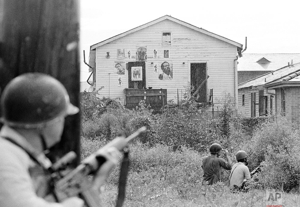 New Orleans policemen take cover as they move in on Black Panther headquarters in New Orleans following a shootout, Sept. 15, 1970. Shooting erupted as police moved in to make arrests. (AP Photo/Jack Thornell)