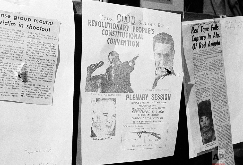 """One of the rounds of shots fired by Philadelphia police, Aug. 31, 1970 in a raid on a Black Panther headquarters ripped through a poster which had been affixed to the wall of one of the rooms, announcing the upcoming Black Panther convention in Philadelphia over the weekend. The poster said here was """"Three Good Reasons for a revolutionary people's constructional convention"""" and showed """"Richard, the pig-hearted Nixon"""" the Cisco kid, Mussolini Rizzo and """"Pig (John) Harrington"""", head of the Fraternal Order of Police. (AP Photo/Bill Ingraham)"""