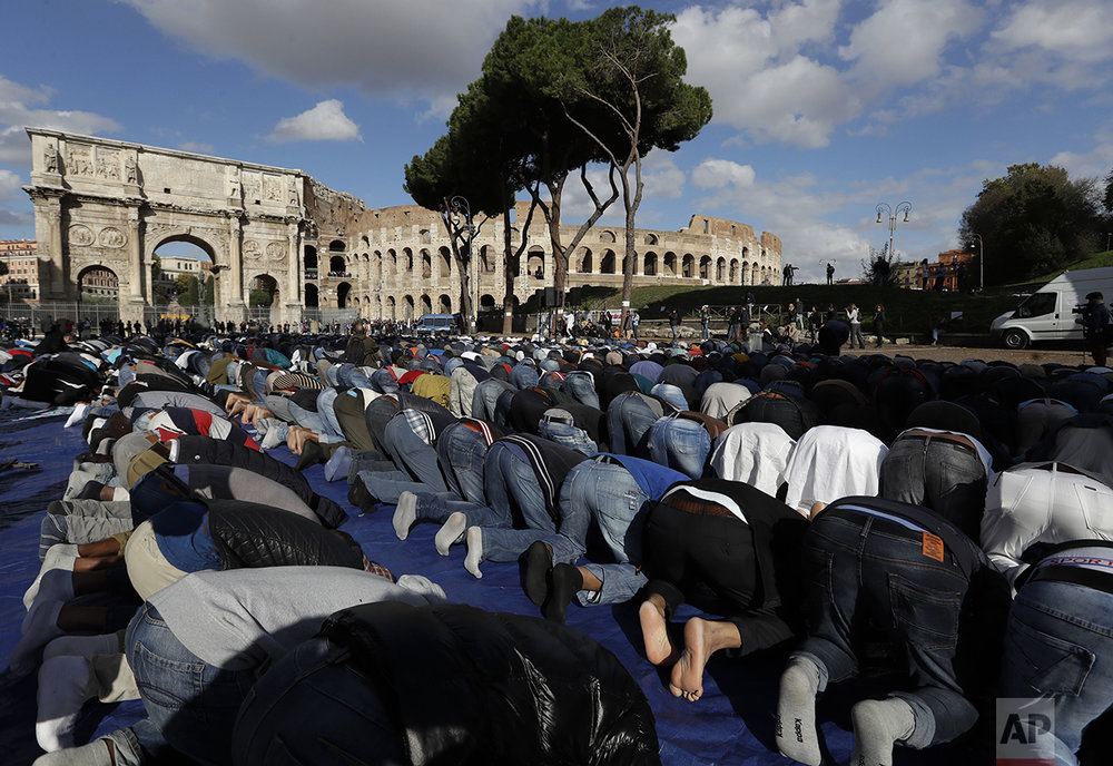Men attend Friday prayers during a demonstration near Rome's ancient Colosseum on Friday, Oct. 21, 2016. The Muslim community of Rome gathered by the historic landmark to pray and protest the closures of mosques and other places of worship. (AP Photo/Alessandra Tarantino)