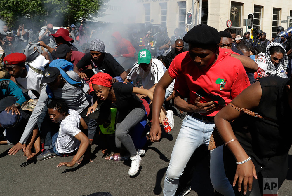 Students run for cover as police fired stun grenades and rubber bullets in an attempt to disperse them during a protest, in Johannesburg, South Africa, Wednesday, Sept. 21, 2016. South African police on Wednesday set off stun grenades and threw tear gas at stone-throwing students from a leading university who were demonstrating for free education.  (AP Photo/Themba Hadebe)