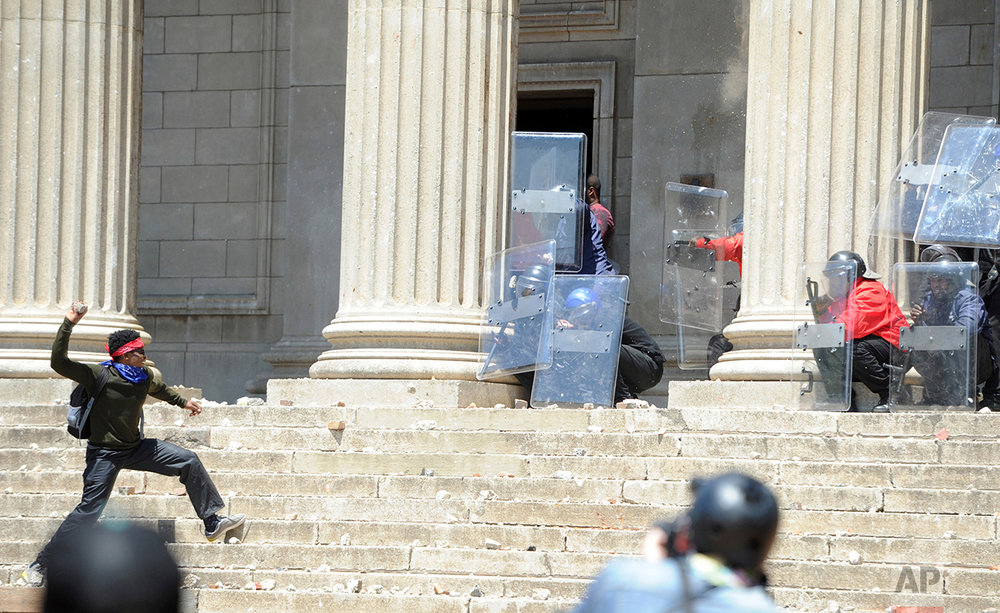 A student, left, hurls a stone at police and private security on the University of the Witwatersrand campus in Johannesburg South Africa  on Monday, Oct. 10, 2016. Tear gas and water cannon were fired as hundreds of students protested at the university amid a bitter national dispute with university managers and the government over demonstrators' demands for free education. (AP Photo)