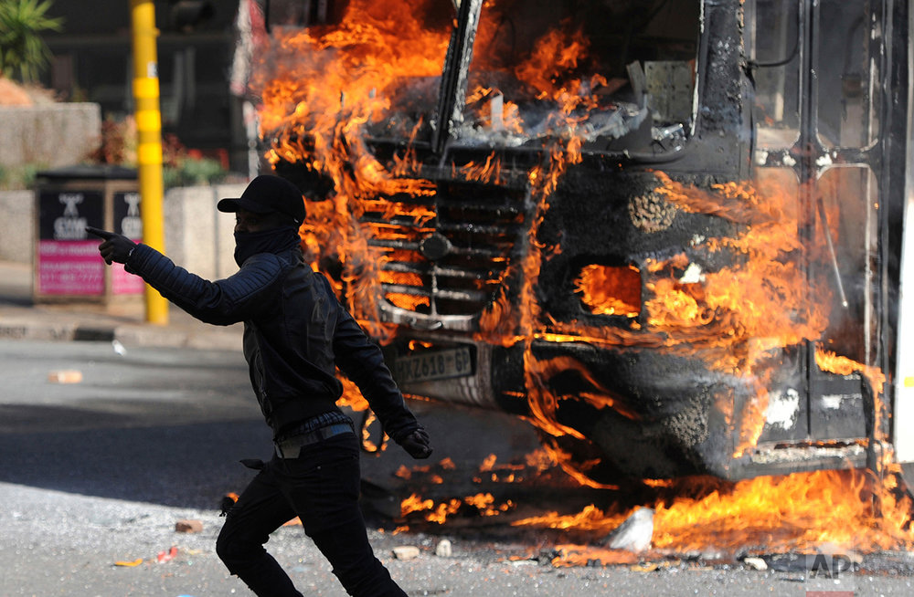 A protesting student runs past a burning bus off campus outside the University of the Witwatersrand in Johannesburg, South Africa on Monday, Oct. 10, 2016. Tear gas and water cannon were fired as hundreds of students protested at the university amid a bitter national dispute with university managers and the government over demonstrators' demands for free education, forcing student into the neighboring city streets. (AP Photo)