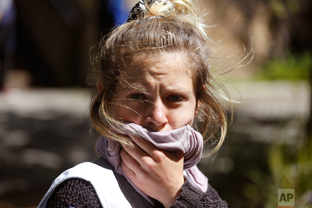 A woman covers her mouth after a stun grenade was used by South African police, after students broke windows at the University of Cape town campus in Cape Town, South Africa, Monday, Oct. 17, 2016. The University of Cape Town re-opened Monday after closing because of security concerns, but police were on campus and used a stun grenade to disperse protesters outside a university building. (AP Photo/Schalk van Zuydam)