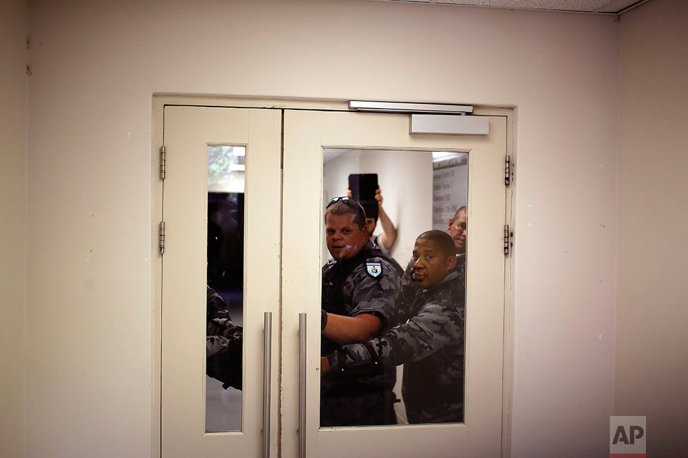 Security guards keep a door closed as they try and prevent students from entering a building at the University of Cape town campus in Cape Town, South Africa, Monday, Oct. 17, 2016. The University of Cape Town re-opened Monday after closing because of security concerns, but police were on campus and used a stun grenade to disperse protesters outside a university building. (AP Photo/Schalk van Zuydam)