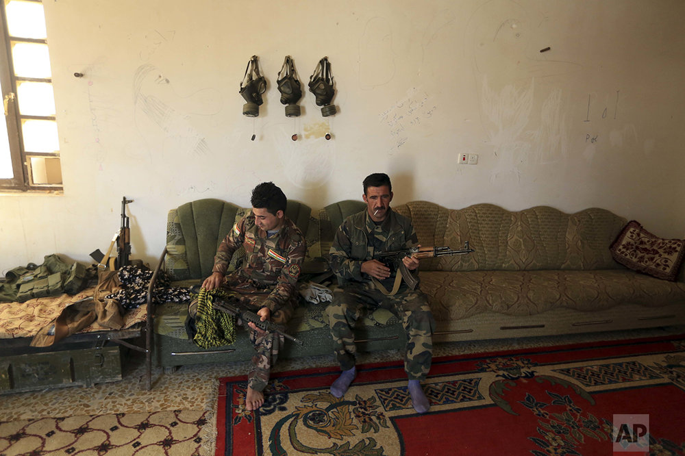 Iraqi Kurdish Peshmerga fighters clean their weapons outside Bartella, Iraq, Friday, Oct. 21, 2016. By Thursday, the Iraqi forces had advanced as far as Bartella, a historically Christian town some nine miles (15 kilometers) from Mosul's outskirts. (AP Photo/ Khalid Mohammed)