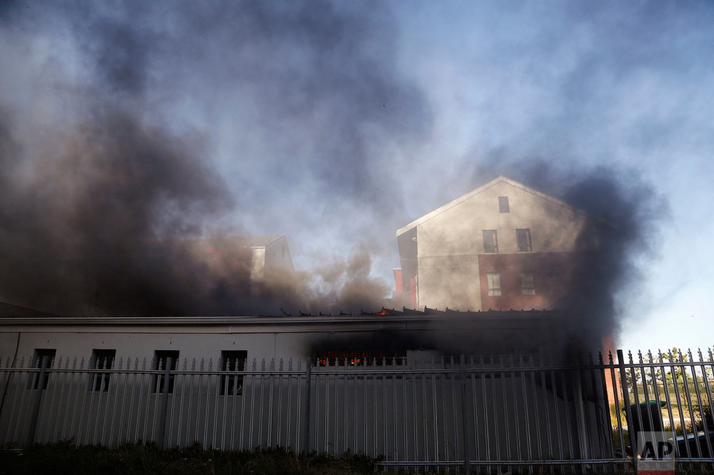 A building burns as students protest at the University of Western Cape campus in Cape Town, South Africa, Wednesday, Oct. 19, 2016. While there is widespread support for the idea of free education, the South African government says it can only cover fee increases for poor students next year and has been harshly critical of student protests involving vandalism and stone-throwing. (AP Photo/Schalk van Zuydam)