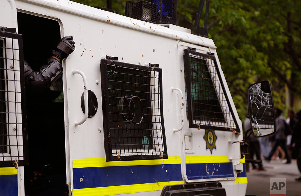 A policeman puts his hand outside his van while providing security at the University of Cape Town, as students protest for free education by disrupting classes in Cape Town, South Africa, Tuesday, Oct. 18, 2016. The University of Cape Town re-opened Monday after closing because of security concerns, but police were on campus and used a stun grenade to disperse protesters outside a university building. Another building was evacuated because of vandalism by protesters who tossed sewage in the corridors, said the statement. (AP Photo/Schalk van Zuydam)