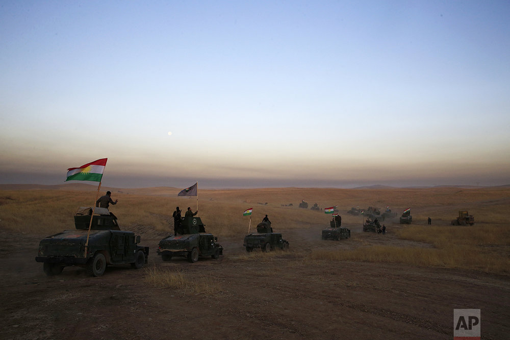In this Monday, Oct. 17, 2016 photo, Peshmerga convoy drives towards a frontline in Khazer, about 30 kilometers (19 miles) east of Mosul, Iraq. In the week since Iraq launched an operation to retake Mosul from the Islamic State group, its forces have pushed toward the city from the north, east and south, battling the militants in a belt of mostly uninhabited towns and villages. In the heavily mined approaches to the city they met with fierce resistance, as IS unleashed suicide truck bombs, rockets and mortars. (AP Photo/Bram Janssen)