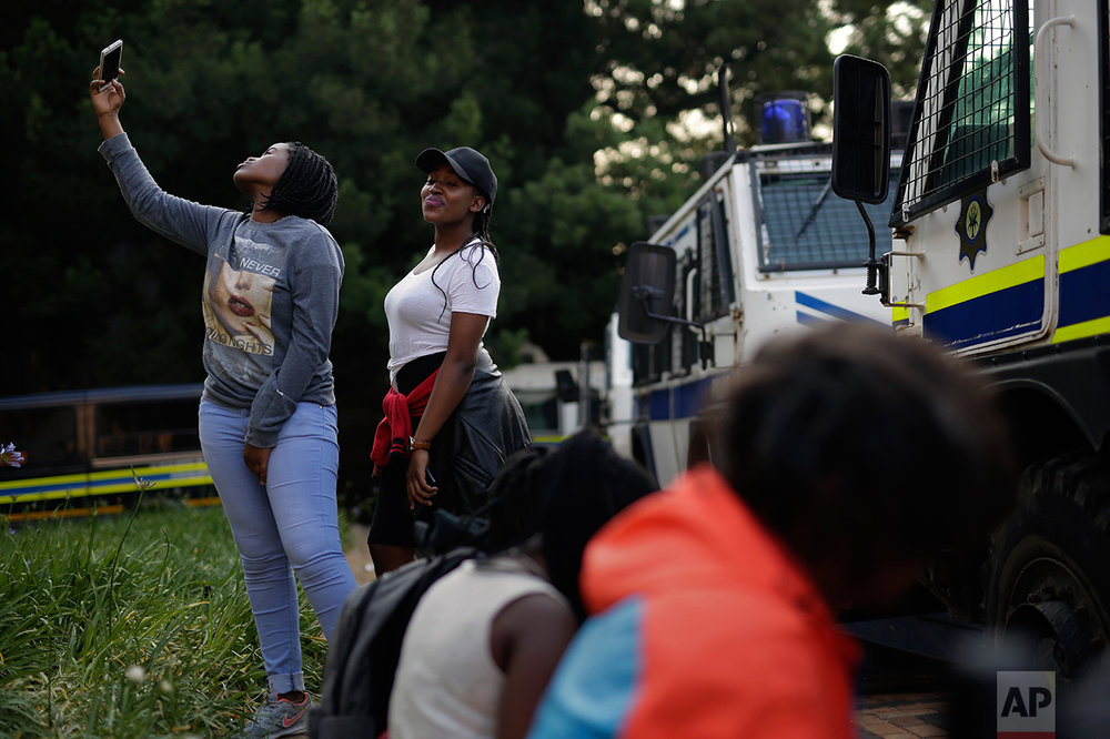 Two students at the University of the Witwatersrand in Johannesburg take a selfie in front of police vehicles stationed on campus Thursday, Oct. 20, 2016. Sometimes violent protests for free education have hit many campuses in South Africa since last month. Some universities are struggling to finish the academic year because of the unrest. (AP Photo/Jerome Delay)