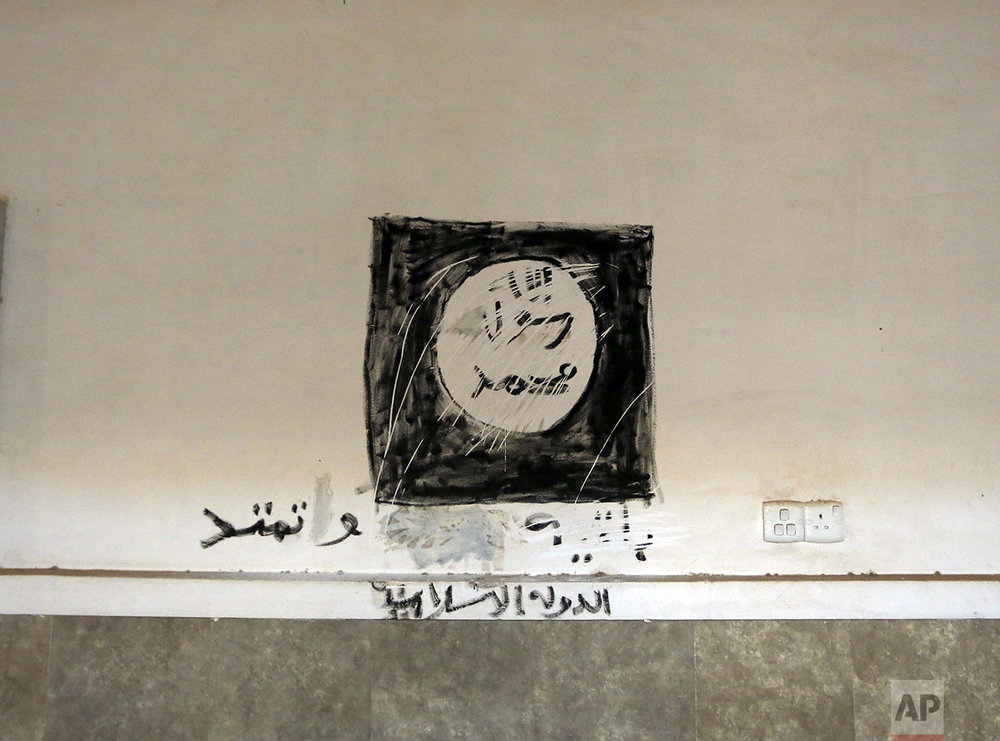 "Islamic State graffiti that reads: ""There is no God but Allah, Muhammad is the Messenger of Allah - Islamic State,"" is seen inside the main church in Bartella, Iraq, Friday, Oct. 21, 2016. By Thursday, the Iraqi forces had advanced as far as Bartella, a historically Christian town some nine miles (15 kilometers) from Mosul's outskirts. (AP Photo/Khalid Mohammed)"