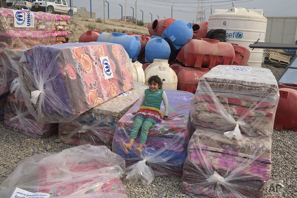 A girl sits on a pile of mattresses at a camp for displaced families in Dibaga, near Mosul, Iraq, Monday, Oct. 24, 2016. The campaign to retake Mosul comes after months of planning and involves more than 25,000 Iraqi troops, Kurdish forces, Sunni tribal fighters and state-sanctioned Shiite militias. It is expected to take weeks, if not months, to drive Islamic State militants out of Iraq's second largest city, which is still home to more than a million people. (AP Photo/Marko Drobnjakovic)