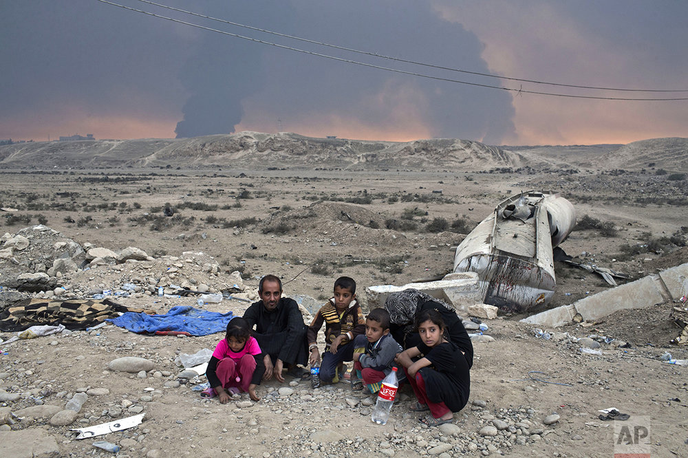 Internally displaced persons sit at a checkpoint as smoke rises from the burning oil wells in Qayyarah, about 31 miles (50 km) south of Mosul, Iraq, Sunday, Oct. 23, 2016. Islamic State fighters torched a sulfur plant south of Mosul, sending a cloud of toxic fumes into the air that mingled with oil wells the militants had lit on fire to create a smoke screen. (AP Photo/Marko Drobnjakovic)