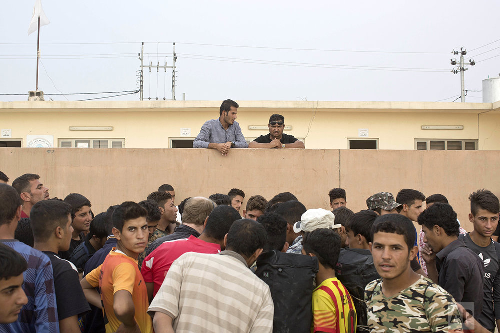 People gather as aid is being distributed at a camp for displaced families in Dibaga, near Mosul, Iraq, Monday, Oct. 24, 2016. The campaign to retake Mosul comes after months of planning and involves more than 25,000 Iraqi troops, Kurdish forces, Sunni tribal fighters and state-sanctioned Shiite militias. It is expected to take weeks, if not months, to drive Islamic State militants out of Iraq's second largest city, which is still home to more than a million people. (AP Photo/Marko Drobnjakovic)
