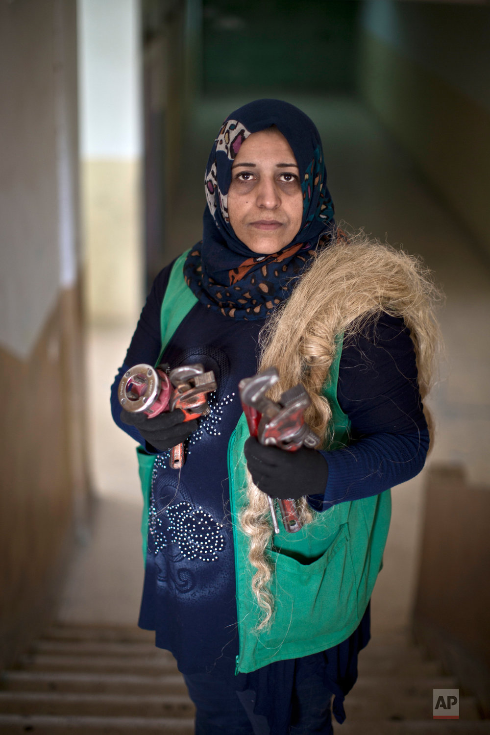 Jordanian plumber Maryam Mutlaq, 41, poses for a picture in a school in Zarqa, northeast of Amman, Jordan, Monday, March 21, 2016. (AP Photo/Muhammed Muheisen)