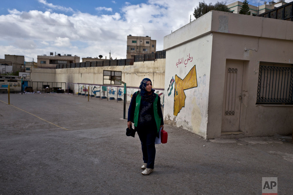 In this Monday, March 21, 2016 photo, Jordanian plumber Maryam Mutlaq, 41, arrives to a school in Zarqa. Mutlaq's choice of career is rare for the Arab world where traditional gender roles make men the main breadwinners and confine most women to certain jobs - teachers, nurses, low-level government clerks. Five years ago, the Arab Spring brought the hope of more opportunities for women. Yet that promise has not panned out, analysts and activists say, and in some cases spreading violence has even led to a backlash. (AP Photo/Muhammed Muheisen)