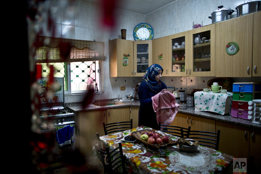 In this Monday, March 21, 2016 photo, Jordanian plumber Maryam Mutlaq, 41, works in the kitchen of her home in Zarqa. (AP Photo/Muhammed Muheisen)