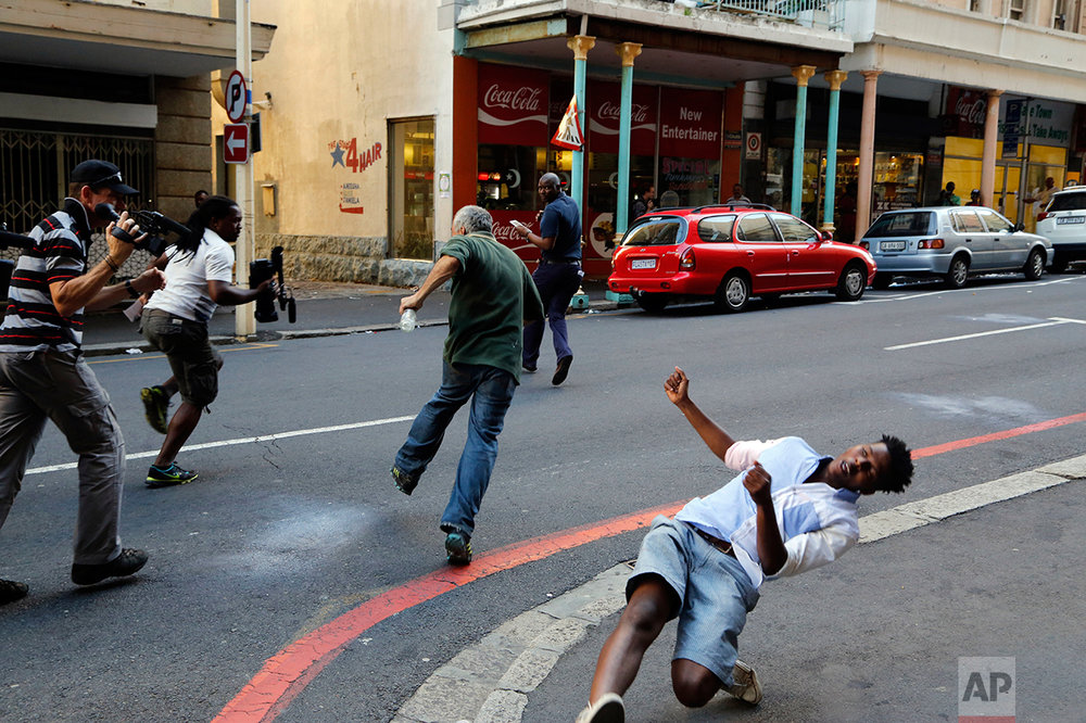 A student protestor, right, is hit by a rock thrown by a fellow protestor in Cape Town, South Africa, Wednesday, Oct. 26, 2016.South African police have used stun grenades to disperse student protesters outside parliament, where the finance minister was giving a budget speech. (AP Photo/Schalk van Zuydam)