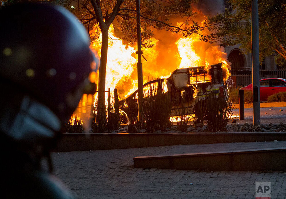 A riot policeman watches as a police vehicle burns in Braamfontein, Johannesburg, South Africa, Tuesday, Oct. 25, 2016. Rioters in South Africa set a police vehicle on fire Tuesday and stoned vehicles near a Johannesburg university that has been the scene of sometimes violent protests by students demanding free education. The violence broke out in streets near the University of the Witwatersrand at around the same time that student protesters met and marched off the campus, South African media reported. (AP Photo/Yeshiel Panchia)