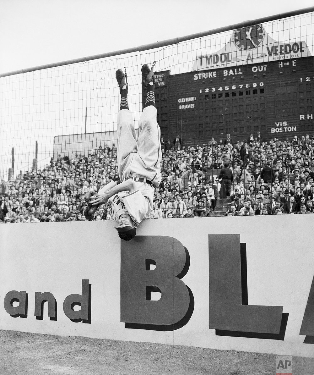 Jackie Price, Cleveland Indian clown, catches ball while strapped upside down to screen at the first day of Boston Braves vs. Cleveland Indians World Series in Boston on Oct. 6, 1948. (AP Photo/Frank C. Curtin)
