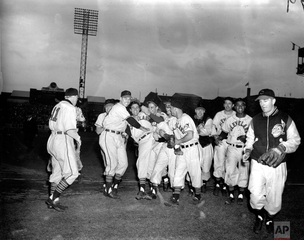 In this Oct. 7, 1948, photo, Cleveland Indians pitcher Bob Lemon, center,  is cheered by his teammates after the Indians defeated the Boston Braves in the second game of the 1948 World Series in Boston. Congratulating Lemon at left, facing camera, is manager Lou Boudreau, and at right is pitcher Bob Feller. (AP Photo)