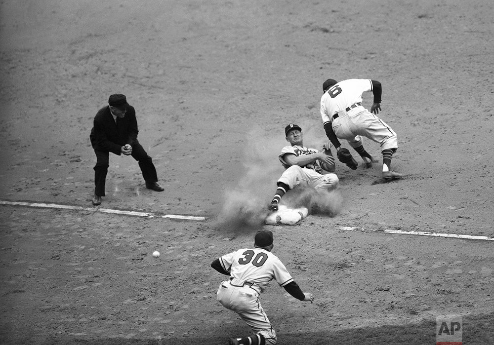 Bob Elliott, Boston third baseman, comes into third base on his back as the ball (lower left) skips past Ken Keltner, Cleveland third baseman, in the seventh inning of the fifth World Series game in Cleveland, Ohio on Oct. 10, 1948. Elliott got up and scored. Manager Billy Southworth (30) is third base coach. (AP Photo)