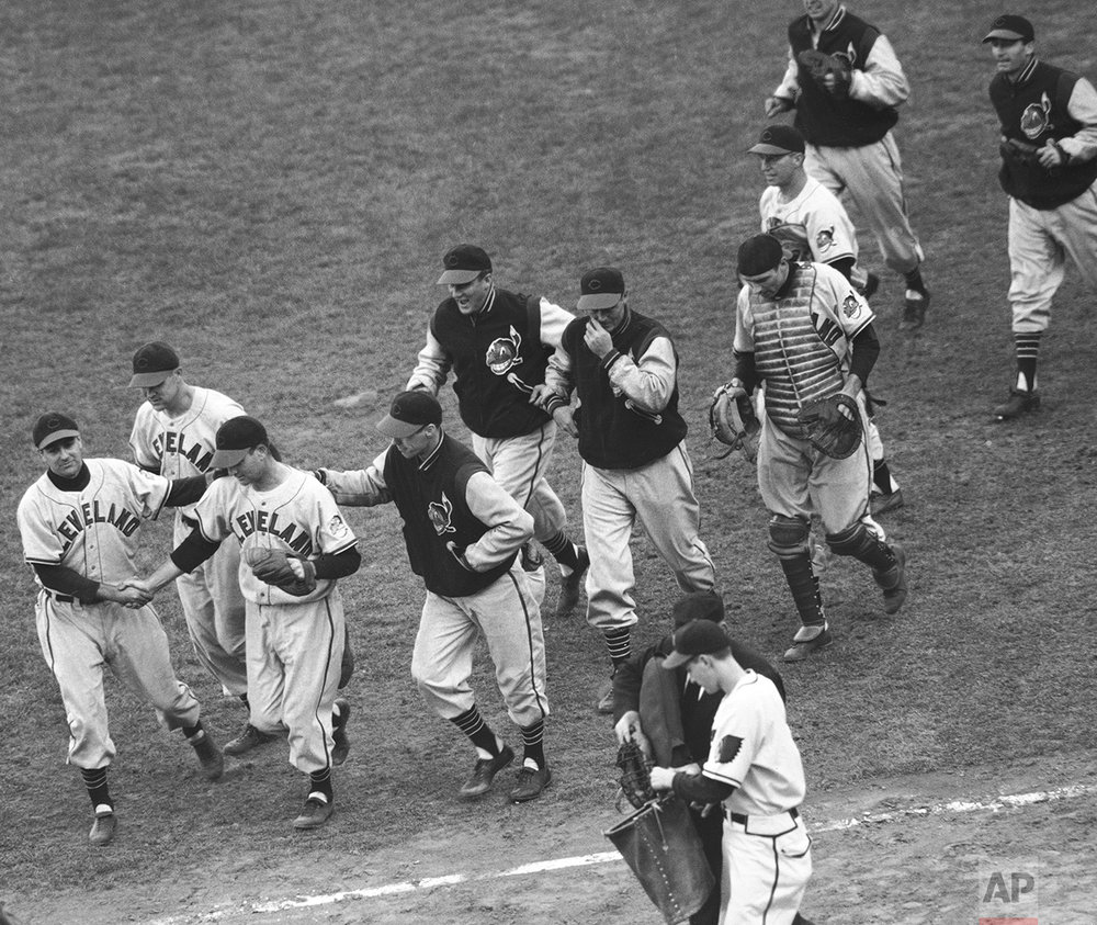 Phil Masi, Boston Braves catcher, clutches his cap as he crosses the plate to score the only run of the game in the World Series opener with the Cleveland Indians in Boston on Oct. 6, 1948.   Masi scored from second on Tommy Holmes single to left field in the eighth inning of the game enabling the Braves to beat the Indians, 1-0.  Watching Masi are Bob Feller (No.19), Indians pitcher, Alvin Dark, Braves shortstop, and Umpire George Barr. (AP Photo)
