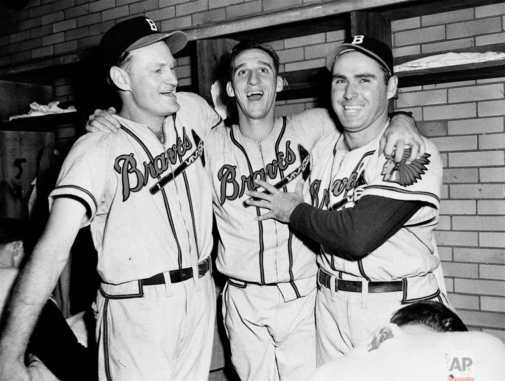 Winning pitcher Warren Spahn, center, of the Boston Braves is flanked by joyous teammates Bob Elliott, left, and Tommy Holmes in the dressing room in Cleveland, October 10, 1948, after an 11 to 5 win over Cleveland in the fifth World Series game.  Spahn allowed only one hit in 5 and 2/3 innings of relief pitching. Elliott clouted two home runs. (AP Photo)