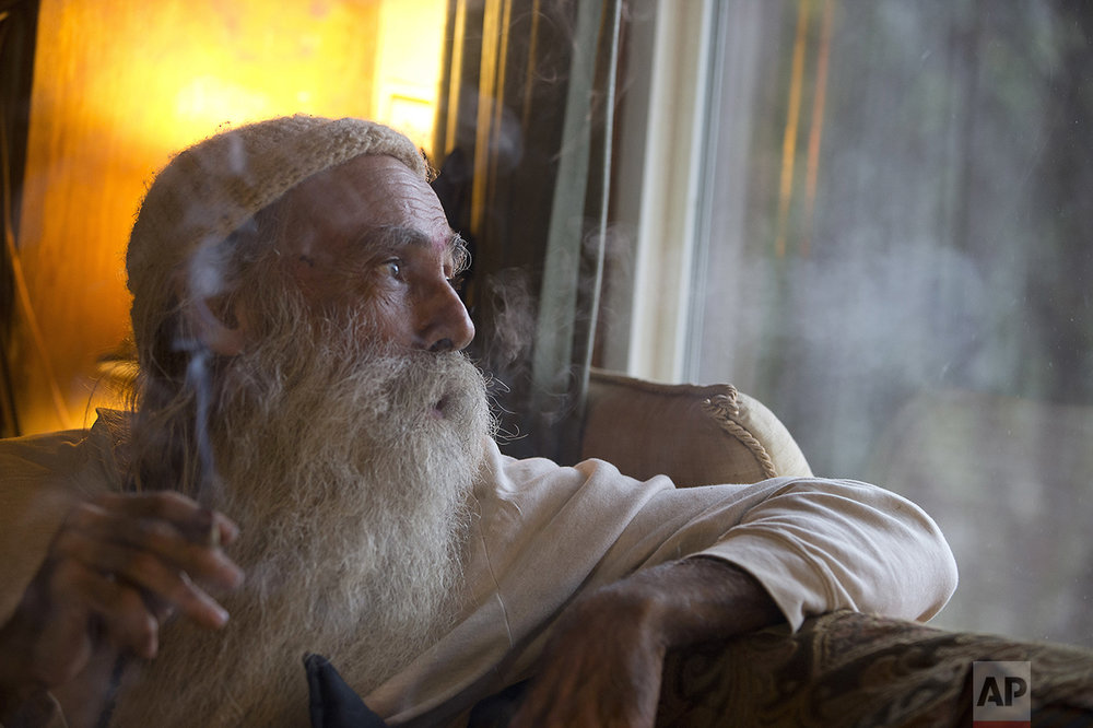 """In this Thursday, Oct. 13, 2016 photo, Swami Chaitanya looks out the window while smoking a """"grower's joint"""" marijuana cigarette at his home near Laytonville, Calif. Chaitanya and his wife, Nikki Lastreto, who grow their """"Swami Select"""" medical marijuana, support the passage of Proposition 64, the Nov. 8 ballot initiative, which would legalize the recreational use of marijuana. (AP Photo/Rich Pedroncelli)"""