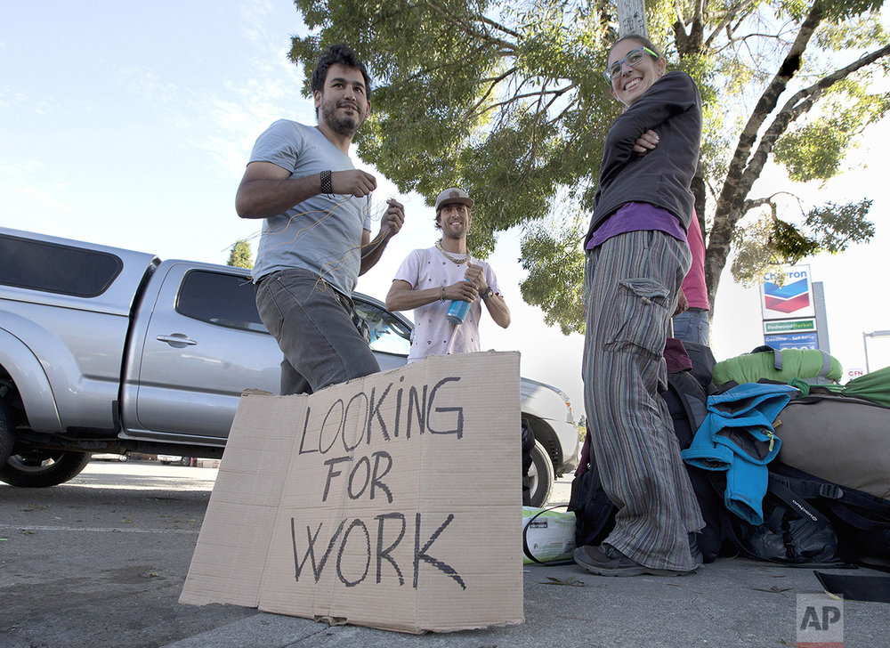 """In this Wednesday, Oct. 12, 2016 photo, Rachel Perez, 22, right, who traveled from Spain with three companions seeks work as a marijuana """"trimmer"""" in Garberville, Calif. Perez and her friends are among those that flock to the area seeking work in the marijuana grows. If approved by voters in November Proposition 64, would legalize the recreational use of marijuana. (AP Photo/Rich Pedroncelli)"""