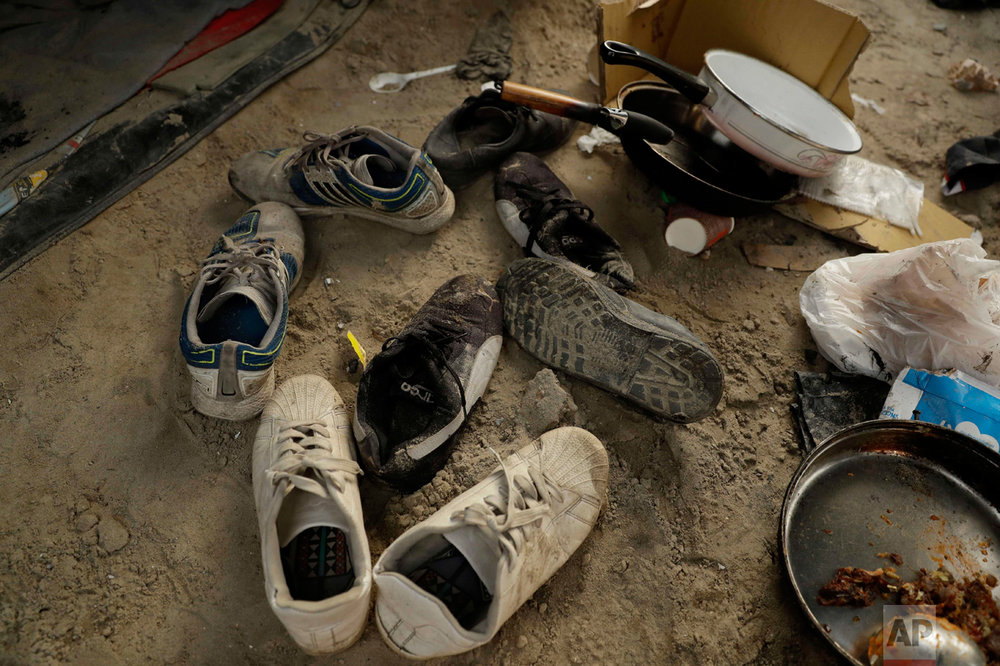 """In this Wednesday, Oct. 26, 2016 photograph, shoes lay abandoned in the entranceway of a tent in the makeshift migrant camp known as """"the jungle"""" near Calais, northern France. (AP Photo/Matt Dunham)"""