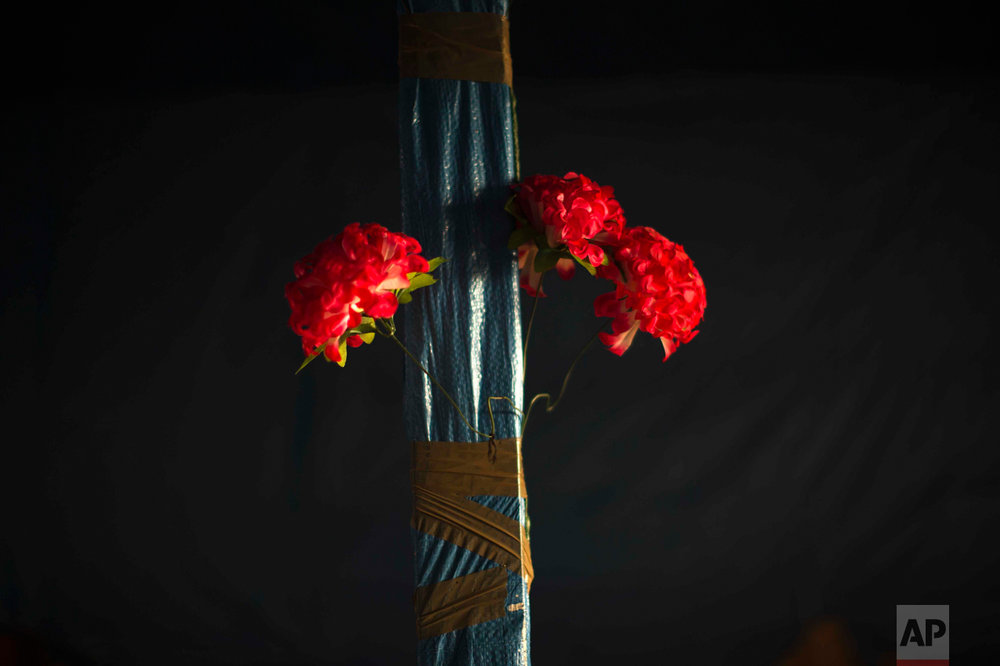 """In this Tuesday, Oct. 25, 2016 photo, plastic flowers are tied with tape to a pole of an abandoned tent at the makeshift migrant camp known as """"the jungle"""" near Calais, northern France. (AP Photo/Emilio Morenatti)"""